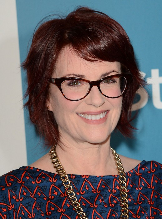 Megan Mullally Layered Short Red Haircut with Side Swept Bangs for Women Over 50