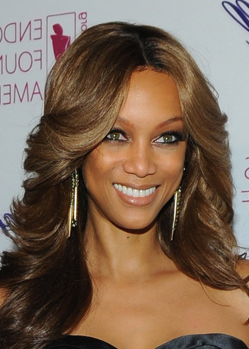 Tyra Banks Caramel Highlighted Feathered Flip Hairstyle for Women