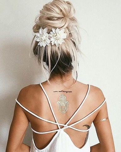 Im calling this a messy bun with a purpose. The flower barrettes (easily hacked or made) add an extra detail to a messy top knot. Even the long dark roots add charm to this style.: